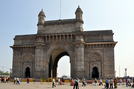 MUMBAI, INDIA - 5 NOVEMBER, 2009: A group of people walk under the Gateway of India in Mumbai on November 5, 2009. The Gateway was built to commemorate the visit of King George V and Queen Mary in 1911.