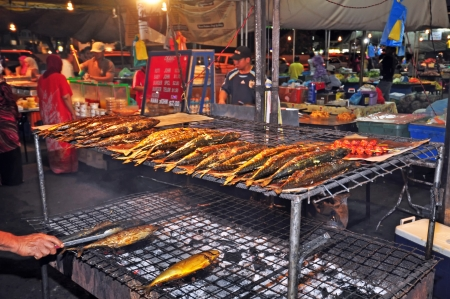tent city: BRUNEI - 30 APRIL, 2010: Grilled fish on a vegetable and food market in the capital of Brunei on April 30, 2010. These markets in Brunei are very known for cheap prices and high quality of goods.