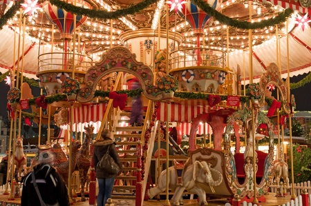 DRESDEN, GERMANY - 20 DECEMBER 2010: An unidentified people enjoy merry-go-round at Christmas market in Dresden on December 20, 2010. It is Germanys oldest Christmas Market with a very long history dating back to 1434.