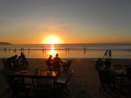 JIMBARAN, BALI - 8 JULY, 2009: Picture of romantic beach restaurant with beautiful sunset sea view on July, 8. Beach restaurants are very popular among tourists.                                Stock Photo - 9144397