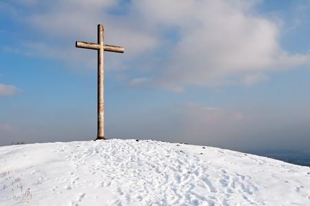 A single cross sitting atop a hill. photo