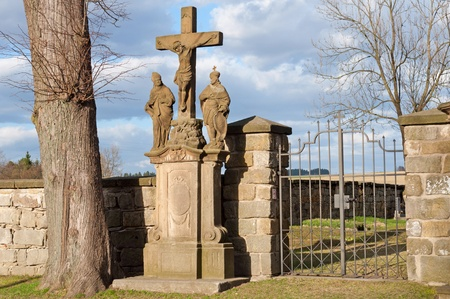 Cemetery entrance with sacral statue during the sunny day. photo