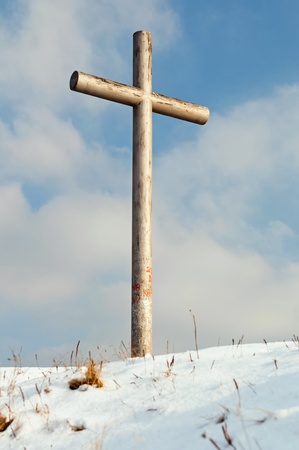 A single cross sitting atop a hill. photo