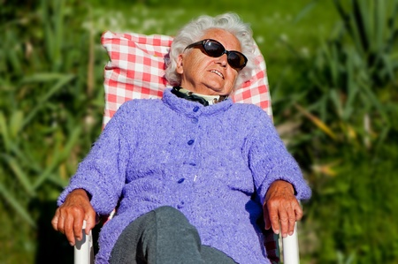 Senior woman has a rest in a chair-bed. photo