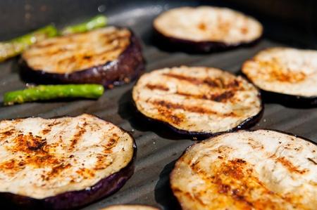 cook griddle: Grilled eggplants and asparagus on a griddle.