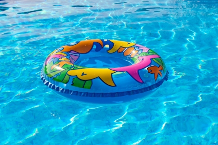 A multicolored swim ring, floating on a blue swimming pool. photo