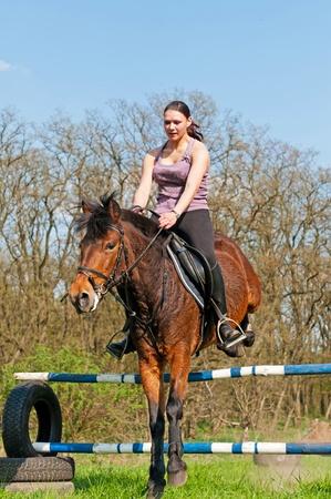 salto de valla: Ni�a bonita y Bah�a caballo durante el d�a soleado.