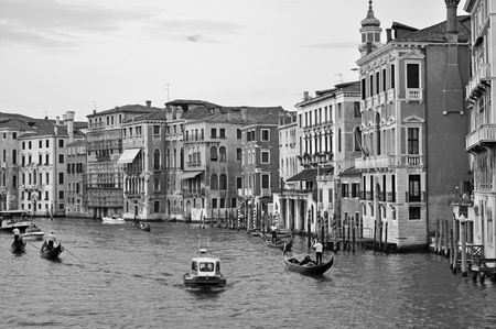 VENICE, ITALY - SEPTEMBER 27, 2009: Tourists enjoy a beauty of Venetian Grand Channel during gondola rides on September 27, 2009 in Venice. The profession of gondolier is controlled by a guild, which issues a limited number of licenses.