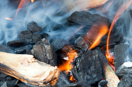 kindling: Wood fire with flames, charcoal and embers.