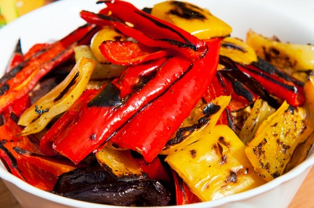 Grilled red, yellow and orange sweet peppers in a bowl.