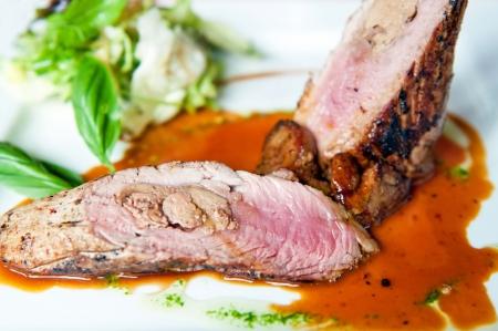 Detail of pork tenderloin prepared on a white plate. photo