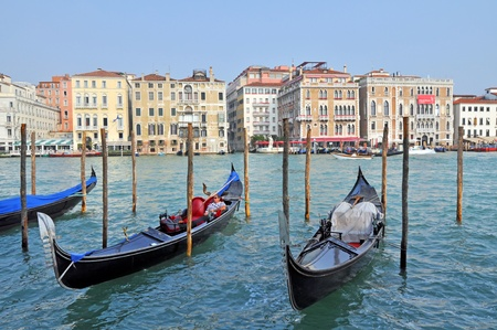VENICE, ITALY - SEPTEMBER 30: Gondolier has a rest in gondola on the Venetian background on September 30, 2009 in Venice, Italy. Profession of gondolier is controlled by a guild which issues a limited number of licenses.