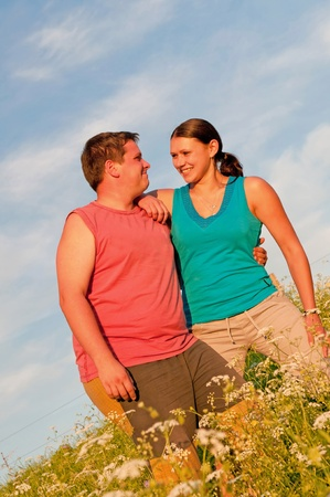 Young couple posing outdoor during the sunset. photo