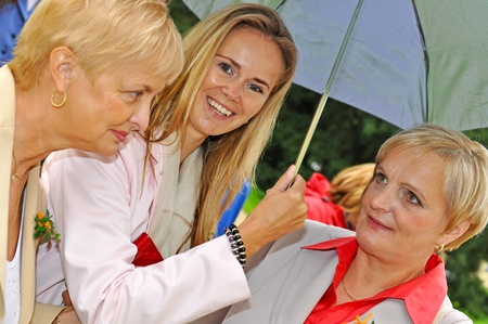 younger: Three women at wedding during the rainy day. Stock Photo