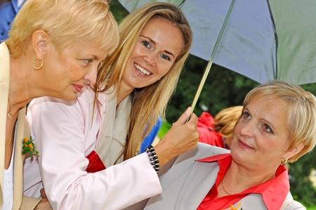 Three women at wedding during the rainy day. photo
