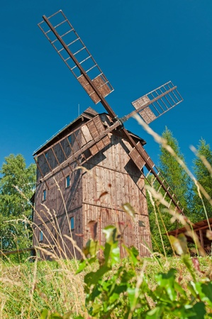 Old traditional wooden windmill hidden in forest. photo