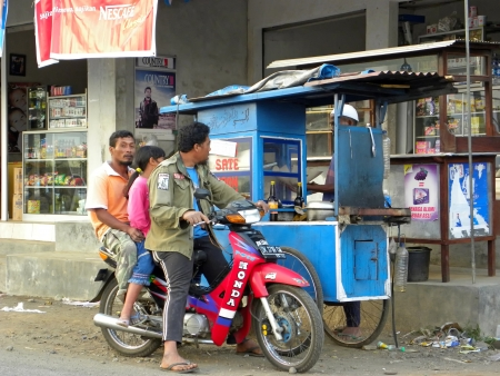jogjakarta: YOGYAKARTA, INDONESIA - JULY 5: View of typical street scene with motorbike and fast food on July 7, 2009 in Yogyakarta, Indonesia. There is nearly 1 million of motorbikes in the whole city.