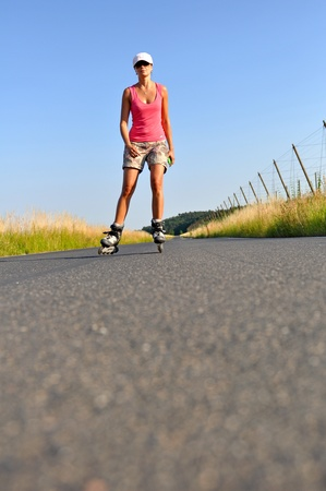 Young woman rollerskating during the sunny day. photo