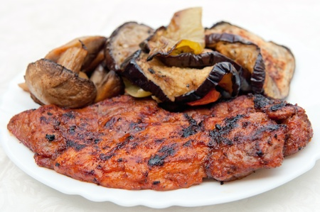 Grilled meat with several pieces of grilled field mushrooms and eggplants.