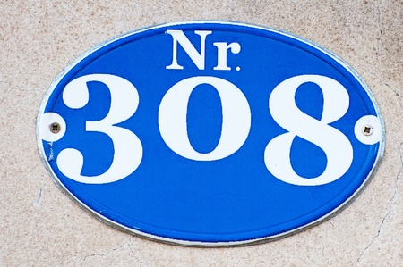 House number 308, white numbers on blue tag. photo