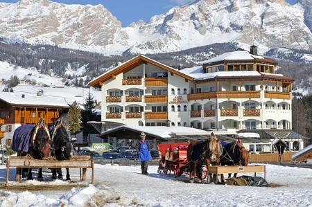 lodges: ALTA BADIA, ITALY - FEBRUARY, 16: Older coachman with traditional alpine sleigh wait for tourists to offer them romantic ride on February 16, 2010 in Alta Badia, Italy. Ride on sleigh is the best way how to recognize alpine resorts.