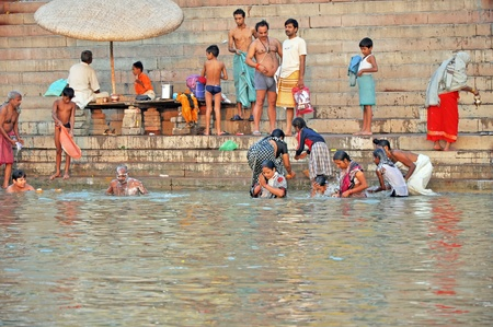 VARANASI, INDIA - 29 OCTOBER, 2009: An unidentified group of Indian people wash themselves in the river Ganga on October 29, 2009.  The holy ritual of washing has to be held every day. Stock Photo - 10390983