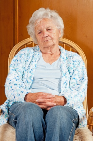 Portrait of sad senior woman in rocking chair. photo