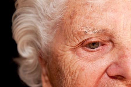 woman face close up: Portrait of a senior woman on a black background.