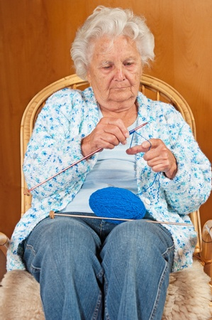 knitting needles: Portrait of a senior woman in rocking chair. Stock Photo