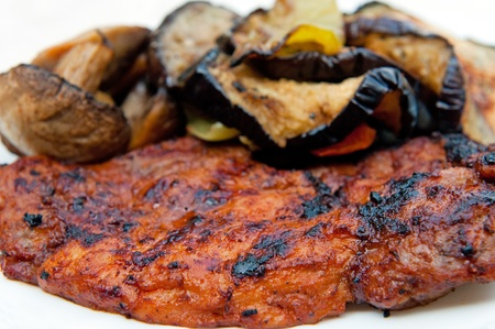 pices: Grilled meat with several pieces of grilled field mushrooms and eggplants.