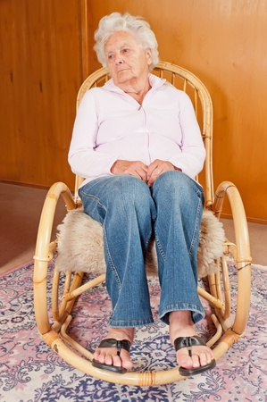 rocking chair: Portrait of sad senior woman in rocking chair.