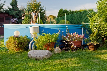 Swimming pool in a garden during the sunset time. photo