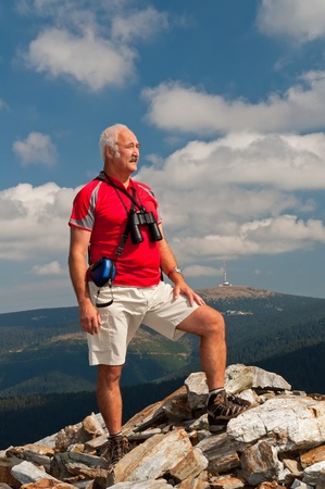 Senior tourist on the top of mountain massif. photo