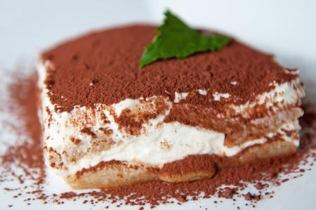 Detailed view of tiramisu cake on a white background.