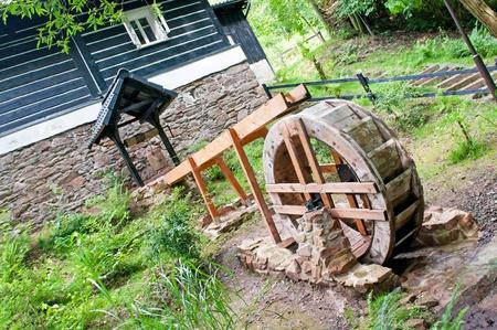 molino de agua: Pequeño molino de agua retro, casa de madera en el fondo.