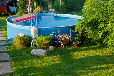 Swimming pool in a garden during the sunset time.