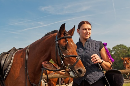 Pretty girl and bay horse during the sunny day. photo