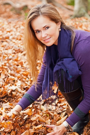 Cute caucasian model with falling leaves in a forest. photo