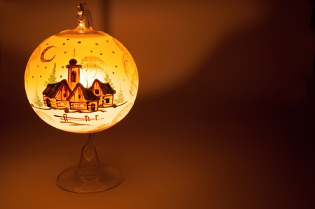 Lighting Christmas decorative ball with candle inside. photo