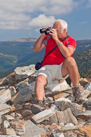 Senior tourist on the top of mountain massif watching landscape through binoculars. Stock Photo - 11563367