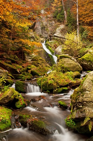 View of a beautiful waterfall during the autumn time. photo