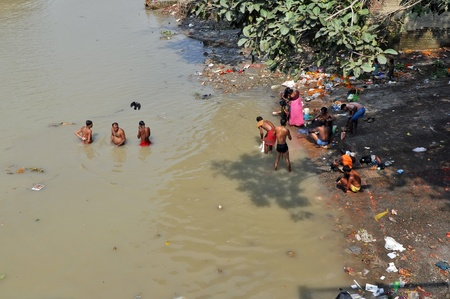 trash the dress: KOLKATA, INDIA - OCTOBER 27: An unidentified group of indian people wash themselves in Hooghly River on October 27, 2009 in Kolkata, India. At present time this river, like the others in India, is being polluted tremendously. Editorial