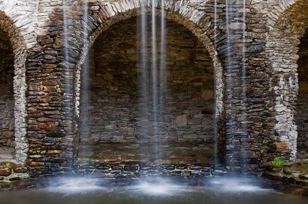 Waterflows in a park, stony wall on the background. Stock Photo - 12374787