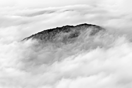Summit of the mountain drowning in clouds, black and white photo. Stock Photo - 12374790