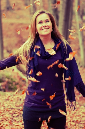 Cute caucasian model with falling leaves in a forest. Stock Photo - 14382521
