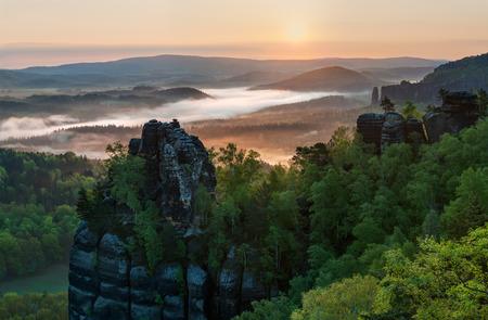 czech switzerland: Vista di una bella alba nebbiosa sulla sommità della collina, foto panoramica.