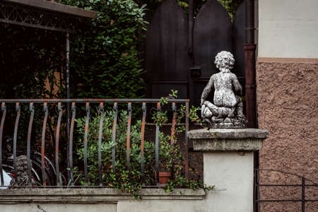 stone statue of angel from behind in italian garden Archivio Fotografico