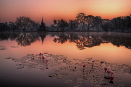 Pagoda in Sukhothai before sunset with lake reflection photo