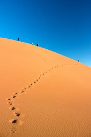 People walking high on dune in Erg Chigaga desert with footprints leading to them photo