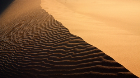 erg: Sand texture with light and shadows and wind-created waves in Erg Chigaga, Morocco Stock Photo
